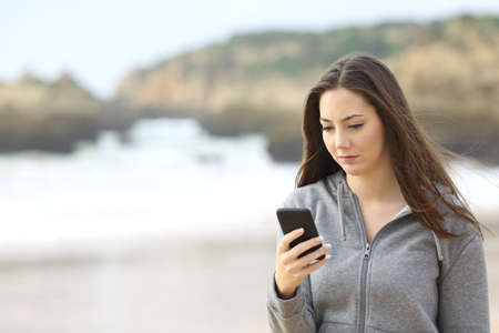 Photo pour Portrait of a sad teenager walking on the beach is checking online the mobile phone waiting for a message in a rainy day - image libre de droit