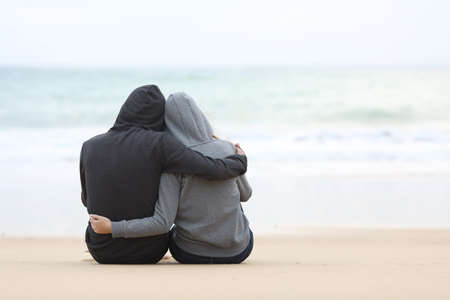 Foto de Rear view of a couple of pensive teenagers hugging and watching the sea sitting on the sand of the beach in a rainy day - Imagen libre de derechos
