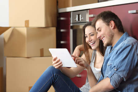 Foto de Couple moving home and buying online with a tablet sitting on the floor in the kitchen - Imagen libre de derechos