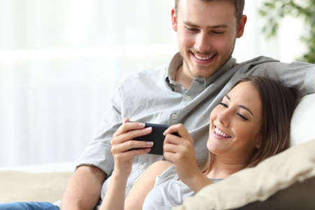 Photo pour Happy couple enjoying media content in a smart phone sitting on a couch at home - image libre de droit