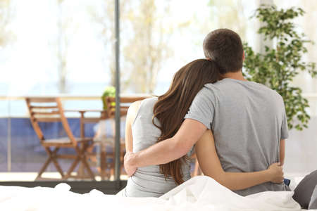Foto de Back view portrait of a happy couple sitting on the bed looking the balcony outdoors through a window of the bedroom of a house - Imagen libre de derechos