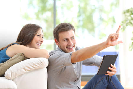 Foto de Happy couple sitting and planning new decoration with a tablet on line at home with a window in the background - Imagen libre de derechos