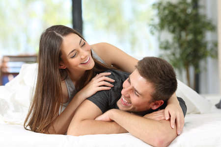 Photo pour Portrait of a happy couple or marriage having fun and joking looking each other on the bed of an hotel room or home - image libre de droit