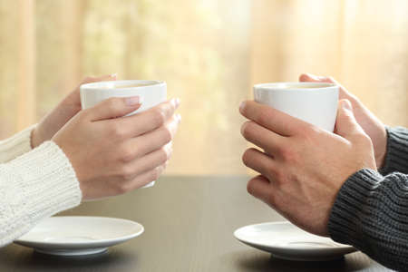 Foto de Profile of hands of a couple holding coffee cups over a table in winter in an apartment with a window in the background - Imagen libre de derechos