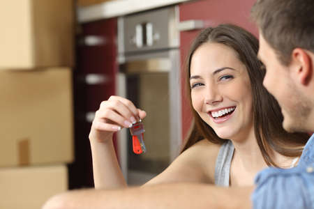 Photo pour Happy new flat couple of owners showing keys sitting in the floor of the kitchen while moving home - image libre de droit
