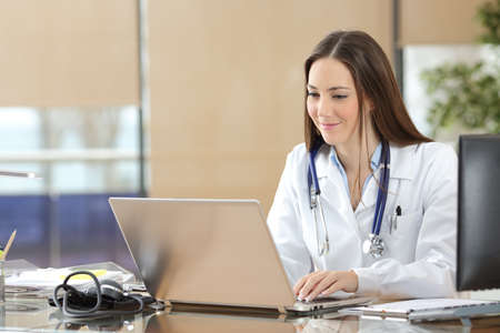Photo for Concentrated doctor working on line with a laptop sitting in a desk in a consultation - Royalty Free Image
