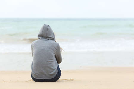 Photo for Back view of one teenager girl thinking alone and watching the sea sitting on the sand of the beach with the horizon in the background - Royalty Free Image