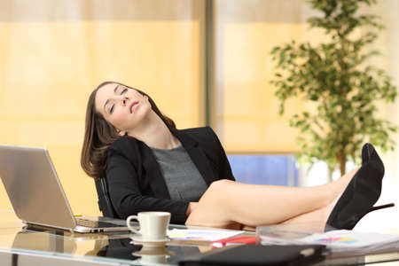 Photo pour Lazy or tired businesswoman sleeping at work with the legs over the table at office - image libre de droit