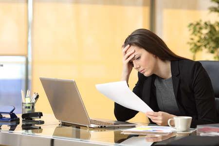 Foto de Worried businesswoman reading a notification while is working sitting in a desk at office - Imagen libre de derechos