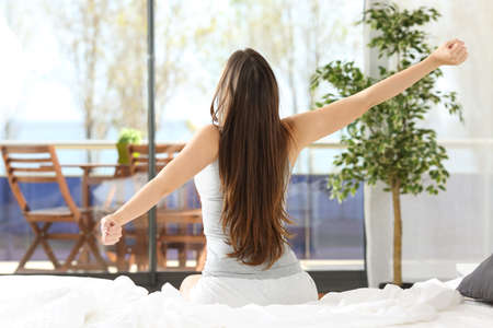 Photo pour Woman stretching arms and waking up sitting on the bed in an hotel or home bedroom looking the sea outdoors through the window - image libre de droit