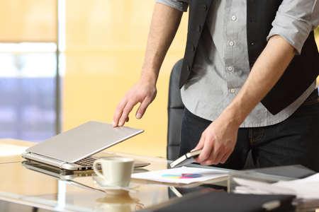 Foto de Close up of a businessman hands leaving work and closing laptop at office - Imagen libre de derechos