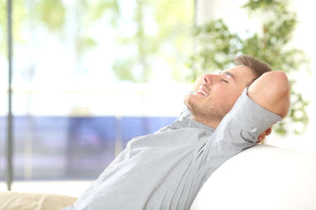 Foto de Side view of a happy attractive man resting and breathing sitting on a couch at home with a window with a green background outdoors - Imagen libre de derechos