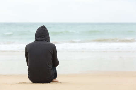 Foto de Rear view portrait of one teenager boy thinking alone and watching the sea sitting on the sand of the beach with the horizon in the background - Imagen libre de derechos