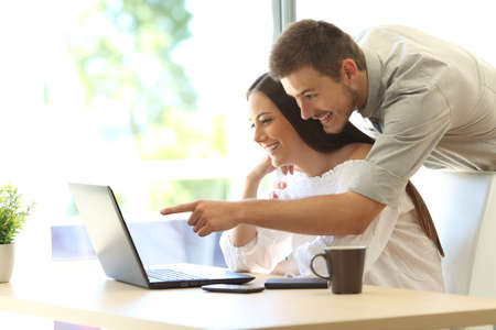 Foto de Side view of a happy couple searching information on line in a laptop on a table at home or hotel room with a window in the background - Imagen libre de derechos