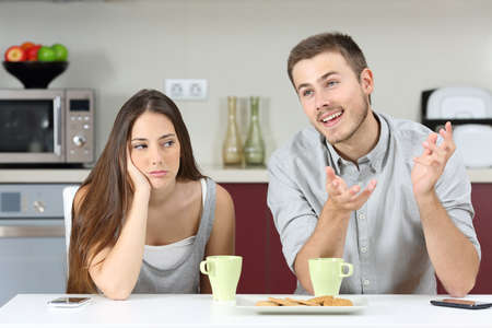 Photo pour Bored wife hearing her husband talking during breakfast in the kitchen at home - image libre de droit