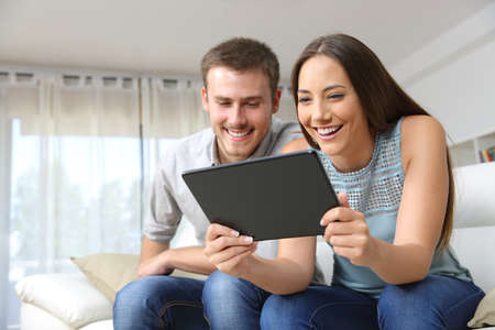 Foto de Couple enjoying media content in a tablet sitting on a couch in the living room in a house interior - Imagen libre de derechos
