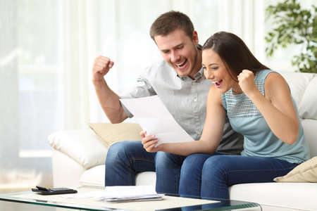 Foto de Excited couple reading a letter together sitting on a sofa in the living room at home - Imagen libre de derechos