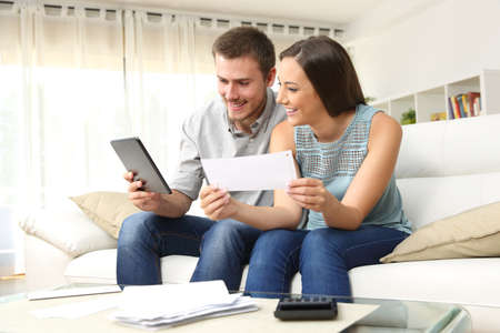 Foto de Happy couple checking bank account on line in a tablet sitting on a couch in the living room at home - Imagen libre de derechos