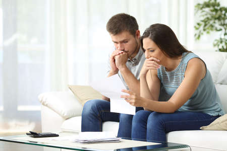 Foto de Worried couple reading an important notification in a letter sitting on a couch in the living room at home - Imagen libre de derechos