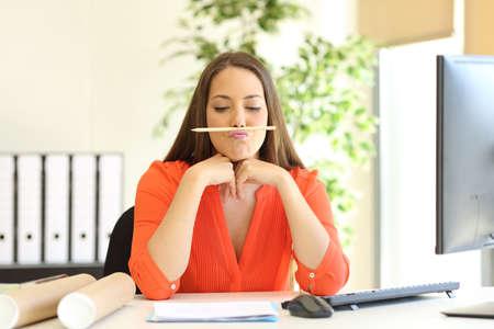 Foto de Bored or incompetent businesswoman playing with a pencil in a desktop at office - Imagen libre de derechos