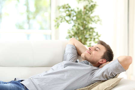 Photo for Relaxed man resting lying on a couch with the hands on the head at home - Royalty Free Image
