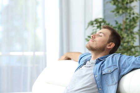 Photo pour Portrait of a casual tired man resting sitting on a couch at home - image libre de droit