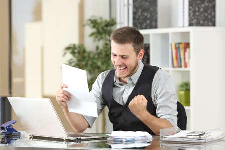 Photo pour Excited businessman reading good news in a a letter in a desktop at office - image libre de droit