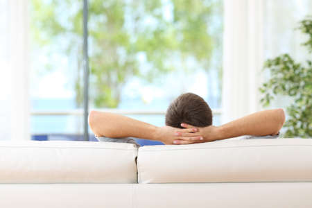 Foto de Rear view of a single man relaxed on a couch at home and looking the green background outdoors through the window in the livingroom - Imagen libre de derechos
