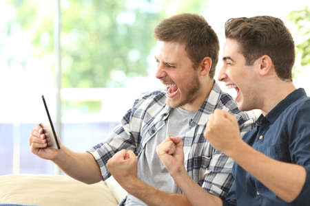 Foto de Two excited friends or roommates watching tv on line in a tablet sitting on a couch in the living room at home - Imagen libre de derechos
