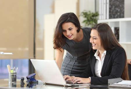 Foto de Two happy businesswomen coworking with a laptop in a desktop at office - Imagen libre de derechos