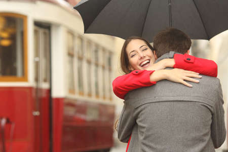 Photo pour Encounter after a travel of a happy couple hugging in the street in a tram station in a rainy day under an umbrella - image libre de droit