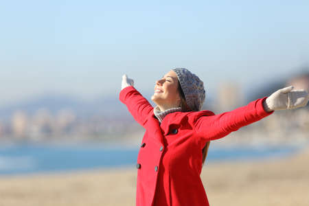 Photo pour Happy woman wearing a red jacket breathing fresh air and raising arms on the beach in a sunny day of winter - image libre de droit
