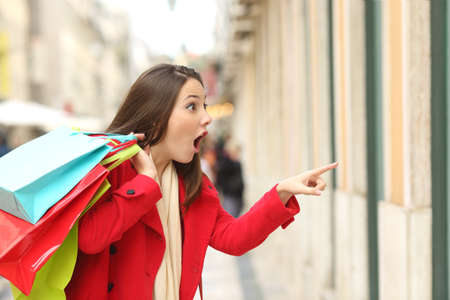 Photo for Amazed shopper opening mouth holding shopping bags watching special offers in stores and pointing in the street in winter - Royalty Free Image