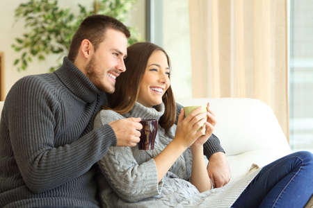 Foto de Affectionate couple wearing sweater holding hot coffee cups sitting on a sofa in the living room at home in winter  - Imagen libre de derechos