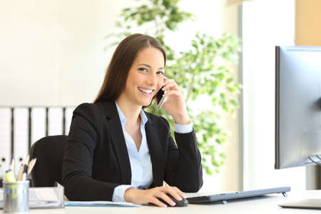 Foto de Portrait of a happy executive wearing suit calling customer service on the phone and looking at camera sitting on a desk in the office - Imagen libre de derechos