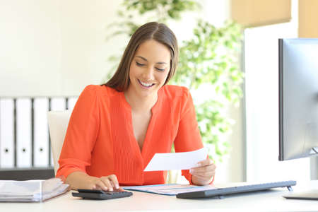 Foto de Businesswoman wearing orange blouse doing accounting and calculating with a calculator in a desktop at office - Imagen libre de derechos