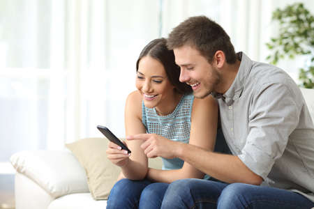 Photo for Relaxed couple or friends using a generic mobile phone together sitting on a sofa in the living room at home - Royalty Free Image
