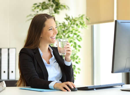 Foto de Happy businesswoman drinking water from a glass and looking through the window at office - Imagen libre de derechos