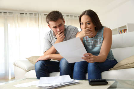 Photo pour Worried couple reading a letter sitting on a couch in the living room at home - image libre de droit