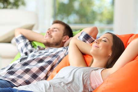 Photo pour Couple or roommates relaxing lying on comfortable poufs in the living room at home - image libre de droit