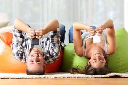 Foto de Funny roommates upside down online with their smart phones lying on orange and green poufs in the living room at home - Imagen libre de derechos
