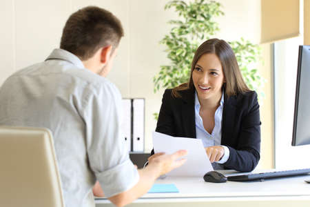 Foto de Businessman talking with his interviewer commenting his skills during a job interview - Imagen libre de derechos