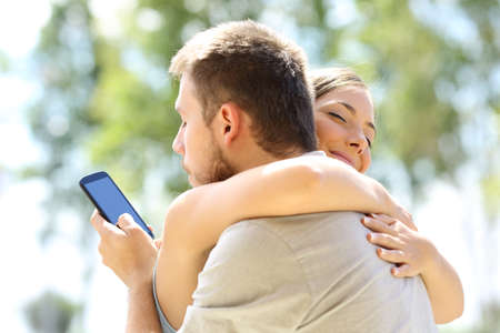 Photo for Cheater texting with his other lover on phone and hugging his innocent girlfriend - Royalty Free Image