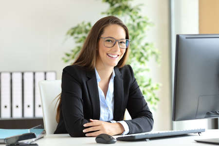 Foto de Happy businesswoman wearing suit and glasses posing sitting in a desktop at office and looking at you - Imagen libre de derechos