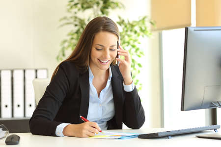 Photo for Happy businesswoman calling on mobile phone and taking notes on a desk at office - Royalty Free Image