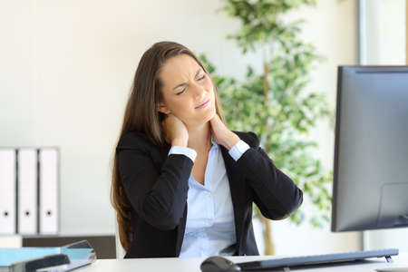 Foto de Businesswoman suffering neck pain sitting in a chair while working with a desktop computer in her workplace at office - Imagen libre de derechos