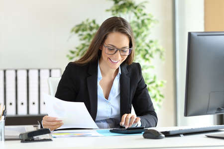 Photo pour Happy businesswoman wearing suit working using a calculator in a desk at office - image libre de droit