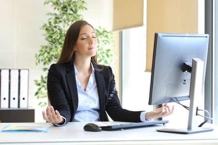 Photo pour Carefree businesswoman relaxing doing yoga exercises at office - image libre de droit