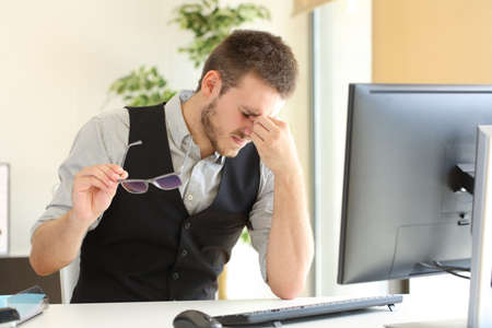 Foto de Businessman suffering eyestrain and holding glasses sitting in a desktop at office - Imagen libre de derechos