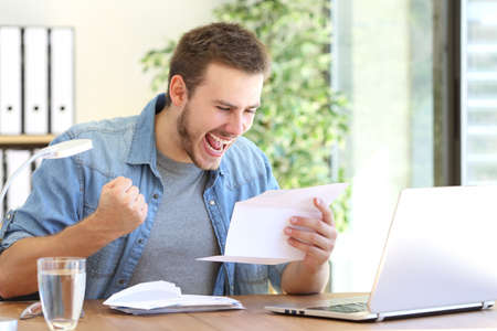 Photo for Casual excited entrepreneur reading a letter with good news in a desktop at workplace - Royalty Free Image